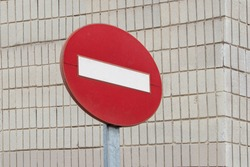 forbidden traffic sign isolated over a white brick wall