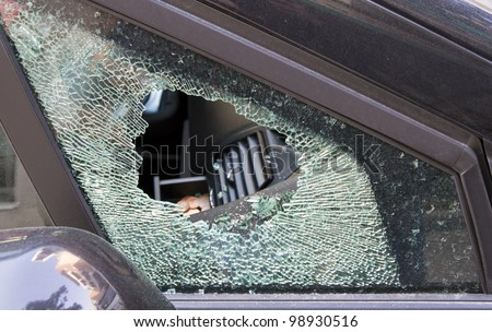 forced car windscreen and broken, stolen by a few coins - stock photo