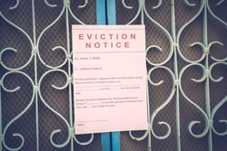 Foreclosed or eviction notice on a main door with blurred details of a house with vintage filter