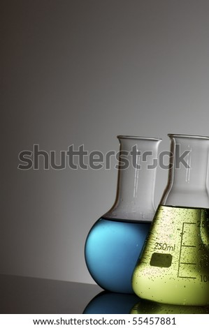 forefront of flasks with brightly colored liquid