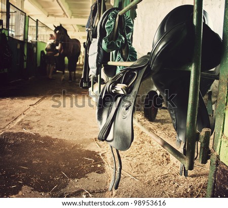 forefront of the saddle, harness, in the background a woman cleans horse