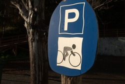 foreground blue bicycle parking sign