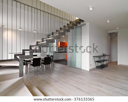 foreground of iron staircase in te modern living room overlooking on the dining room and the kitchen whose floor is made of wood