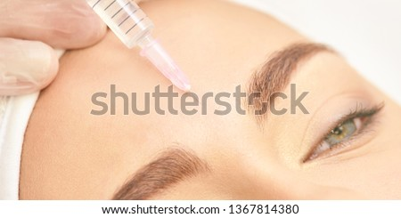 Forehead woman surgery. Anti wrinkle filler. Cosmetology injection. Face skin rejuvenation. Doctor injecting collagen acid.