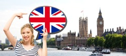foreign language, english, travel, people and communication concept - smiling woman holding text bubble of british flag and pointing finger over london city and big ben tower background