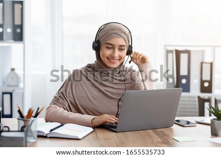 Foreign Languages Online Concept. Portrait Of Smiling Arabic Girl In Hijab And Headset Watching Webinar On Laptop While Sitting In Office