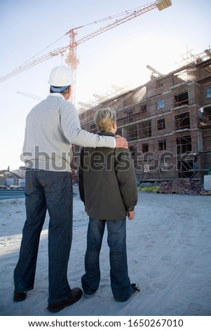 Foreman and boy looking at building under construction