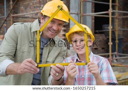 Foreman and boy on construction site with house shaped ruler