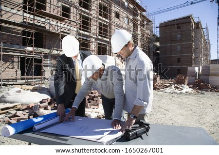Foreman and co-workers looking at blueprints on construction site
