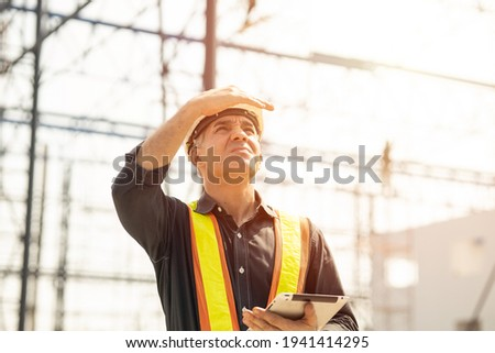 Foreman builder engineer worker looking at large building construction site sunny day hard work. Photo stock ©