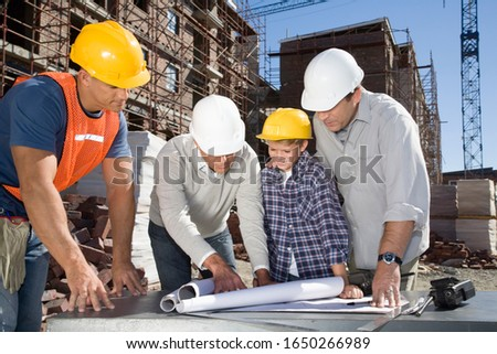 Foreman, co-workers and boy looking at blueprints on construction site