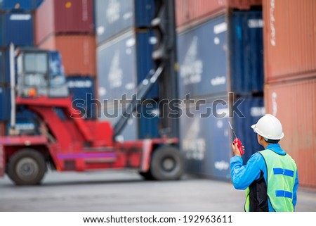 foreman control forklift handling the container box load to big truck selective focust at container box