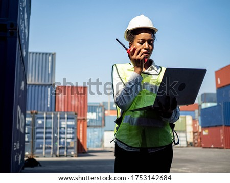 Foreman engineering women africa is holding computer notebook pc tablet and talk telephone about work at warehouse container cargo import export investment technology business  ストックフォト ©