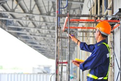 Foreman inspecting scaffolding structure at construction site.