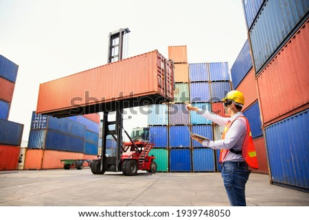 Foreman or Operator Ordering of moving containers with laptop computer. Foreman looking forward on Forklifts in the Industrial Container Cargo freight ship. Look forward. Foto stock ©
