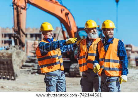 Foreman showing builders something at the construction site by pointing his hand  ストックフォト ©