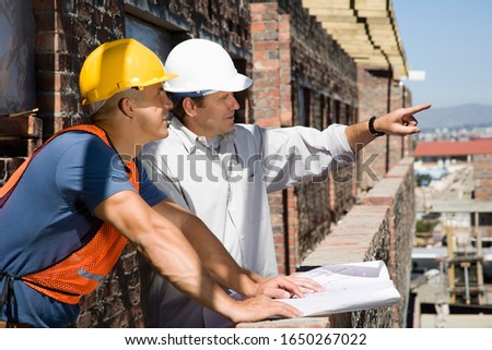 Foreman talking to construction worker on site