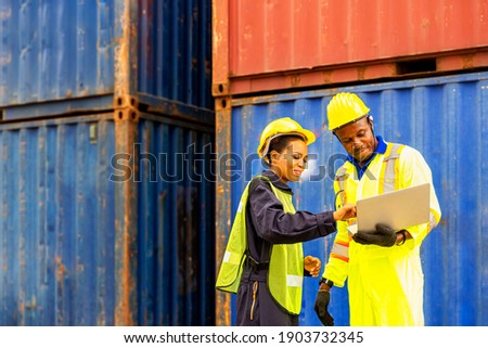 Foreman using laptop computer in the port of loading goods. Foreman talking with worker or laborer in the Industrial Container Cargo freight ship. Photo stock ©