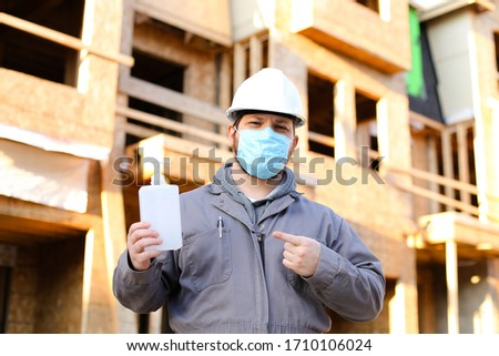 Foreman wearing mask and hardhat showing disinfectant at construction site. Concept of coronavirus protection and social distance at workplace.