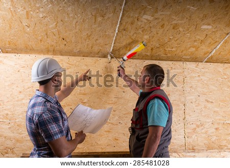 Foreman Wearing White Hard Hat and Holding Building Plans Instructing Worker How to Apply Caulk to Seam in Unfinished Wood Ceiling in New Home