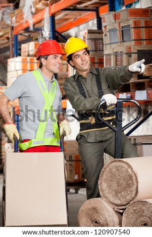Foreman with fork pallet truck showing something to coworker at warehouse