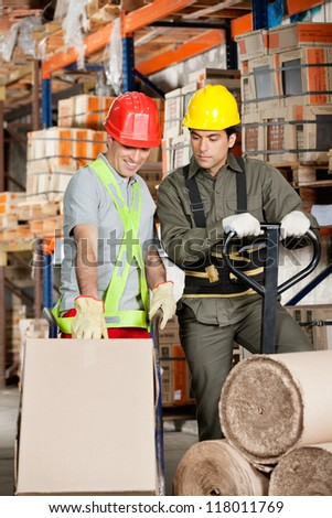 Foreman with handtruck showing something to coworker at warehouse
