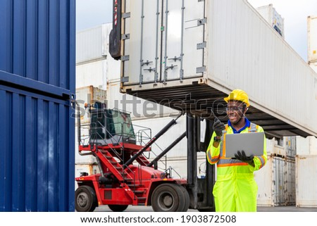 Foreman works with laptop computer radio to communicate with forklift drivers. Foreman using laptop computer in the port of loading goods. Photo stock ©
