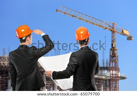 Foremen in a black suit holding a blueprints and looking towards the construction site