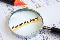 Forensic audit data and magnifying glass on papers.