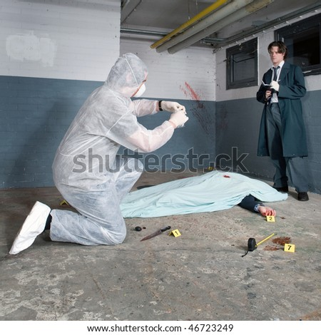 Forensic expert bagging evidence at a crime scene whilst a police inspector is taking notes around the corpse of a murdered businessman