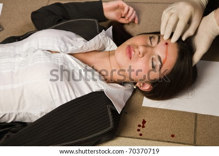 Forensic expert collecting evidence in a crime scene around a dead businesswoman