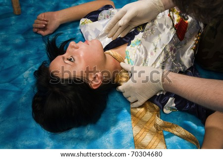 Forensic expert collecting evidence in a crime scene around a strangled woman - stock photo