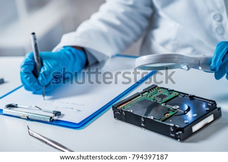 Forensic science expert examining hard drive Stock photo ©