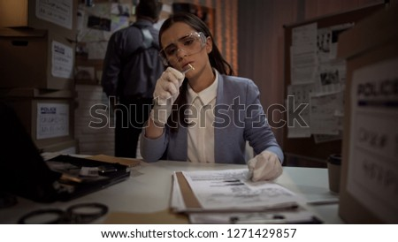 Forensic scientist lady examining the evidence bullet from the crime scene