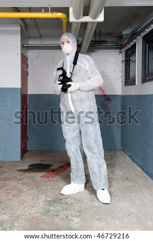 Forensics expert, dressed in a white protective suit, mask and shoe covers, carrying a camera, posing in a basement