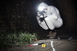 Forensics researcher photographing a blood stained knife at a murder scene