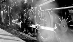 Foreshortened grayscale view of a greasy oily metal valve gear and assembly rods linkage and drive wheels on a decapod steam locomotive engine with a cloud of steam in the foreground