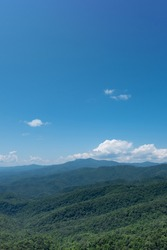 Forest covered foothills of the Blue Ridge Mountains on North Carolina, NC, USA with brilliant blue sky and puffy white clouds