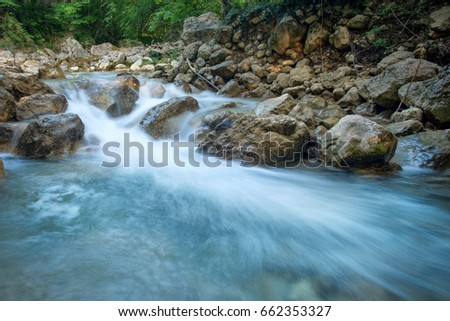 Forest creek with waterfalls. Water cascades over rocks. blue and crystal clear water in mountain river.