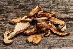 Forest dried edible mushrooms. Dehydrated slices, exquisite ingredient for cooking healthy food. Vintage wooden table, close up
