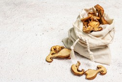 Forest dried edible mushrooms in a linen sack. Dehydrated slices, exquisite ingredient for cooking healthy food. Light colors plaster background, copy space