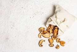 Forest dried edible mushrooms in a linen sack. Dehydrated slices, exquisite ingredient for cooking healthy food. Light colors plaster background, top view