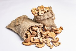 Forest dried edible mushrooms in sackcloth bags isolated on white background. Dehydrated slices, exquisite ingredient for cooking healthy food