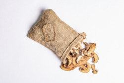 Forest dried edible mushrooms in sackcloth isolated on white background. Dehydrated slices, exquisite ingredient for cooking healthy food