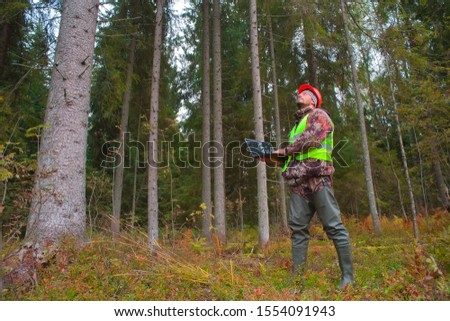 Forest engineer works in the forest on a computer. Work clothes, vest, hard hat, forestry. Stock photo ©