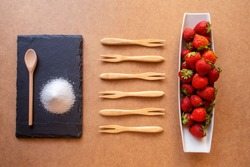 Forest fruits, strawberries and sugar on a white rectangular plate and square slate plate. on a brown base with shades. Wooden forks. Whole strawberries on a plate.