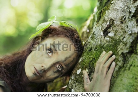 Forest girl embracing beech-tree