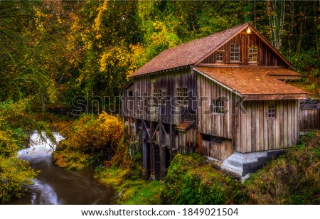 Forest hut in autumn woods. Hut at autumn forest creek. Forest hut autumn view. Autumn forest hut river