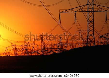 forest of transmission towers over horizon during sunset