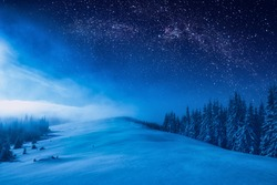 Forest on a mountain ridge covered with snow. Milky way in a starry sky. Christmas winter night.